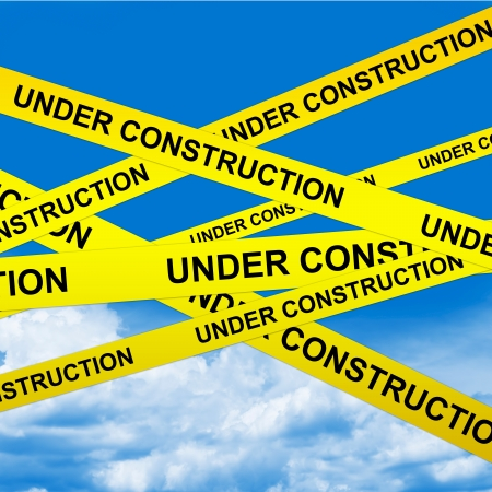 Under Construction Caution Tape With Blue Sky Background photo