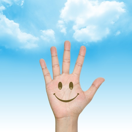 background sky: Hand With Smile Face in Blue Sky Background Stock Photo