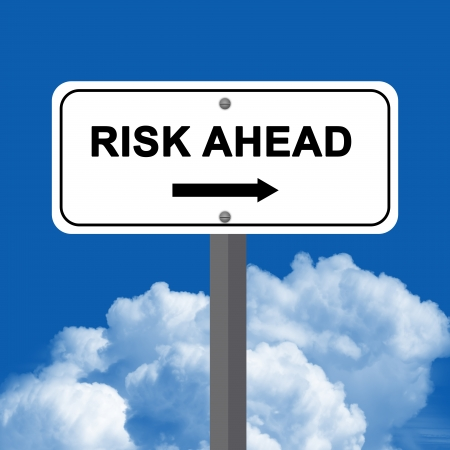 Risk Ahead Street Sign Stand Against A Blue Sky Background photo