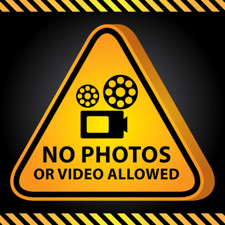 vdo: 3D Yellow Glossy Style Triangle Caution Plate For Safety Present By No Photos or Video Allowed With VDO Camera Sign in Dark Background
