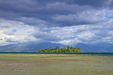 motu: Motu is a small island on the reef, from Moorea island with Tahiti behind the clouds. Stock Photo