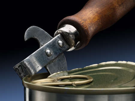 can opener: Ancient can opener and modern tin. Stock Photo