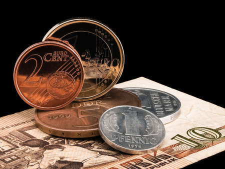 ddr: Coins of GDR  DDR  and the European union on a black background
