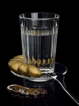 focus stacking: EURO coins near to a thick glass tumbler, a pickle and a fork on a saucer