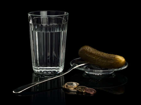 focus stacking: EURO coins near to a thick glass tumbler, a pickle and a fork on a saucer.