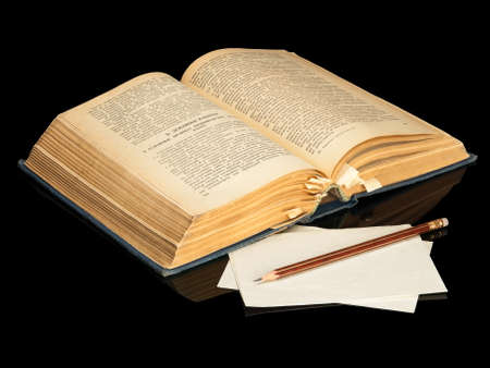 The opened ancient book and pencil on a black background photo