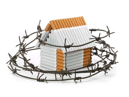 barbed wire isolated: The house constructed of cigarettes behind a barbed wire isolated on white