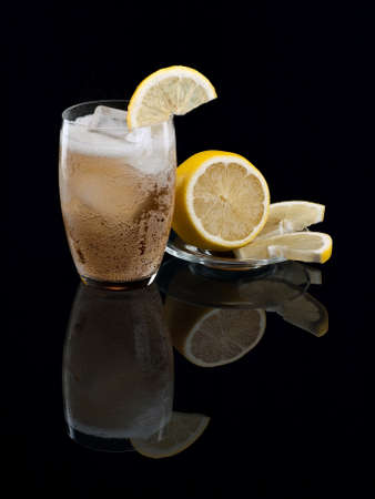 aerated: Lemonade with ice and a lemon on black Stock Photo