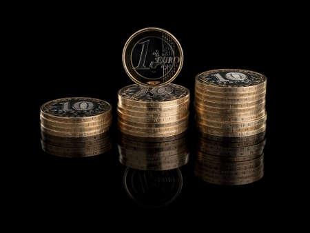 vómito: Tres montones de las monedas rusas y una moneda de euro que se encuentra aislada en el negro Foto de archivo