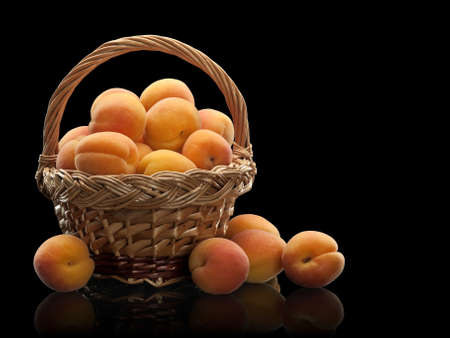 wattled: wattled basket filled with apricots is isolated on black