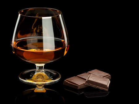 Slices of chocolate and cognac in a glass it is isolated on black