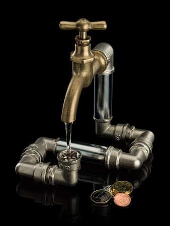 vómito: Monedas de euro y el sistema de agua del grifo de latón se encuentra aislado en negro Foto de archivo