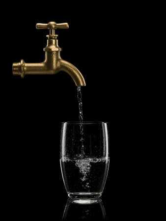 waterpipe: Filling by water of a glass from brass faucet is isolated on black Stock Photo