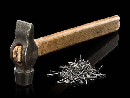 small group of objects: Old hammer with the wooden handle and a heap of nails it is isolated on black Stock Photo