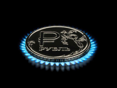 threw: Coin with a symbol of the Russian ruble on a gas flame it is isolated on the black