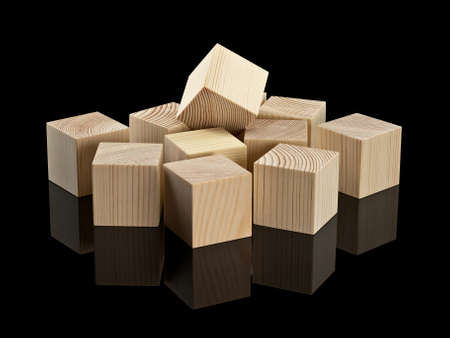 heaped: The wooden cubes, heaped it is isolated on black