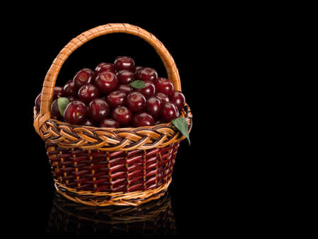 aliments: Basket filled by a cherry it is isolated on black