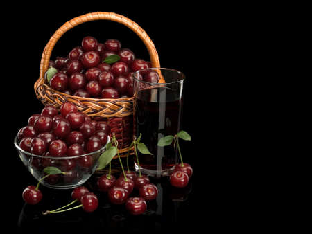 Basket and vase full of a cherry with a glass of cherry juice it is isolated on black Stock Photo