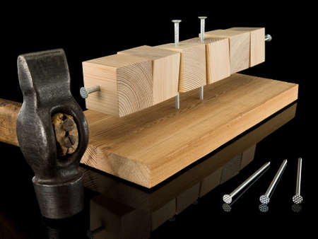 sewn up: Wooden cubes are sewed with a wooden board, nails and a hammer Stock Photo