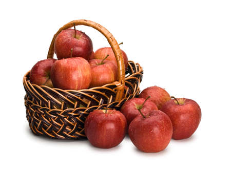 Crop of red apples in wattle basket it is isolated on white
