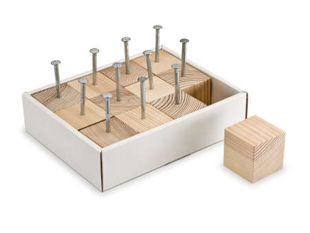 sewn: Eleven wooden cubes are densely sewn in a cardboard box and one cube free Stock Photo