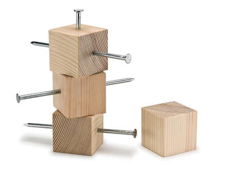 fastened: Three wooden cubes punched by steel nails and one whole cube it is isolated on the white Stock Photo