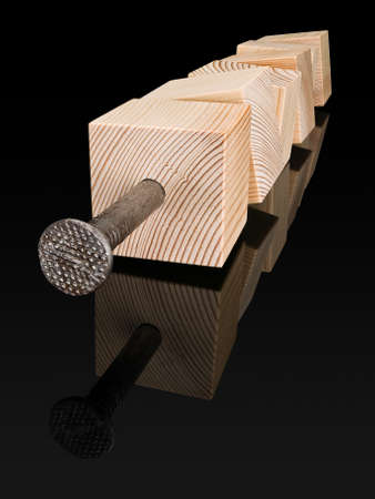 rusty nail: Six wooden cubes are punched by the big steel nail, is isolated on black