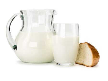 The jug and glass from glass are filled by milk, the white loaf chunk nearby lies, it is isolated on white