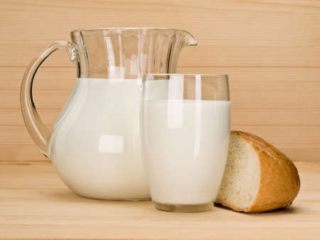 The jug and glass from glass are filled by milk, nearby on a wooden table the white loaf chunk lies.