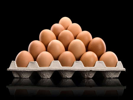 The brown eggs combined by a pyramid in cardboard packing, it is isolated on black