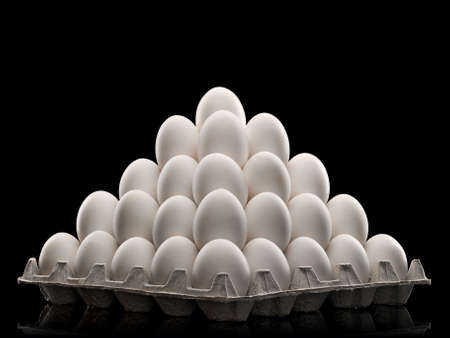 white eggs combined by a pyramid in cardboard packing, it is isolated on black