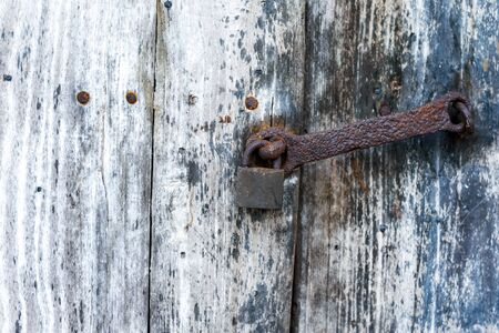 Old rusty padlock in the closed position, hanging on the wooden door