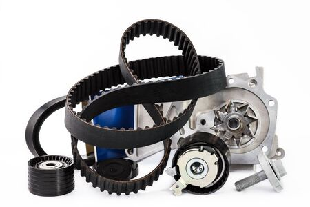 Spare parts for the car. The set of timing belt with rollers and cooling pump on a white background.