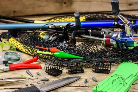 Fishing tackle. Fishing rods, floats, fishing rod holder, knife, fishhooks and landing net on old wooden background.