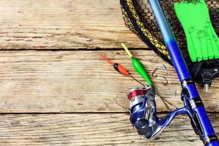 Fishing tackle. Fishing rod, floats, fishing hooks and landing net on old wooden background with free space for text.