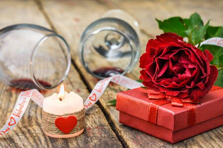 Rose, gift, burning candle and glasses for wine. Valentines Day