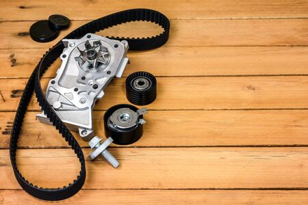Spare parts for the car. The set of timing belt with rollers and cooling pump on a wooden background with free space for text. Stock Photo