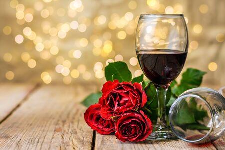 Saint Valentin nature morte. Deux verres de vin et de roses rouges sur une table en bois rustique devant un arrière-plan lumineux flou. Mise au point sélective. Banque d'images