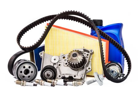 Various spare parts for the car. The set of timing belt with rollers, cooling pump, motor oil, sparking plugs and filters on a white background.