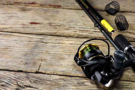 Fishing rod and fishing tackle on old wooden background with free space for text.