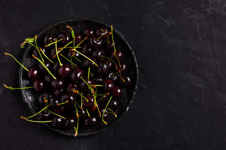 Fresh sour cherries in a black bowl on the dark background with copy space for text. Fresh ripe sour cherries. Top view.