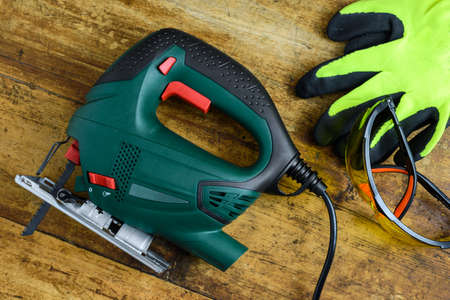A jigsaw power tool, protective glasses, gloves and blades for electric jigsaw on old wooden background. Imagens