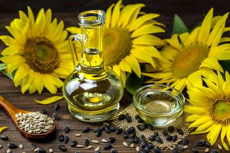 Sunflower oil in a bottle and sunflower seeds near fresh sunflower flower on a wooden background. Selective focus. Stock fotó
