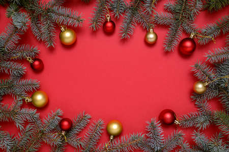 Christmas frame made of fir branches, Christmas baubles on red background with copy space for text. Christmas and New Year concept.