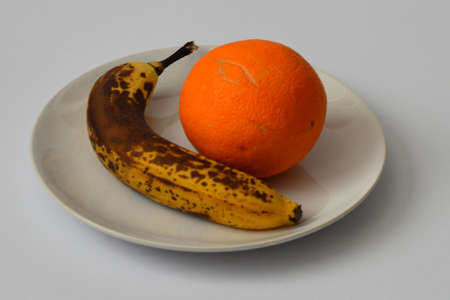 overripe: Overripe banana and orange on the plate on light gray background Stock Photo