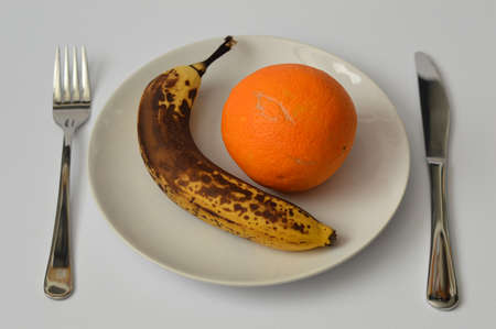 overripe: Overripe banana and orange on the plate with fork and knife on light gray background