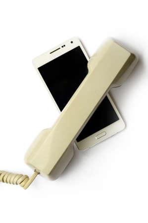 technological evolution: Mobile phone covered by landline handset Stock Photo