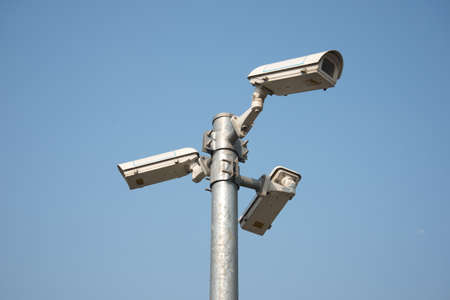 cctv security: Three direction CCTV security camera on iron post blue sky background