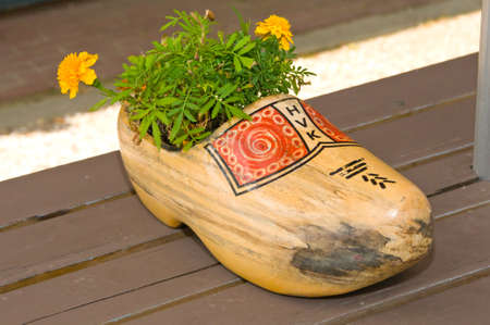 motifs: AMSTERDAM, HOLLAND - JULY 18, 2010: Dutch wooden clog with red motifs painted and yellow flowers inside, photographed in the street.
