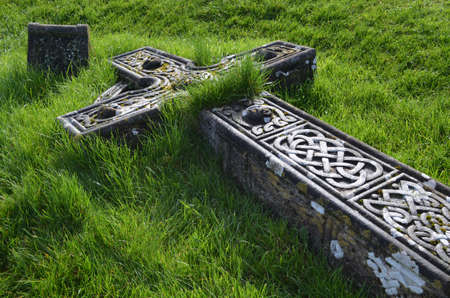 memorial cross: Grass over growing a fallen cemetery cross in Ireland.
